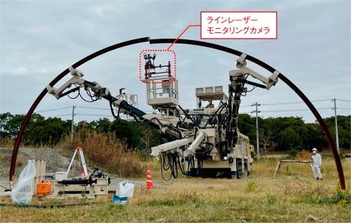 写真1■ 大成建設がアクティオと共同で開発した「T-支保工クイックセッター」工法で、支保部材をつなぐ様子。エレクターの作業用バスケットにラインレーザーとモニタリングカメラを搭載。操縦席で映像を確認しながらエレクターを操作している(写真:大成建設)