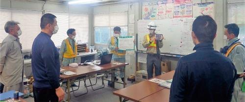 写真1■ 安全注意喚起システムをタブレットで表示し、危険予知活動で災害事例を確認する様子(写真:三井住友建設)