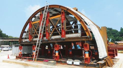 写真1■ 清水建設などが実証実験で組み立てた実物大のプレキャストコンクリートの覆工。現在、専用の架設機材を開発しており、実験ではクレーンを使って部材を設置・連結。組み立て架台に仕込んだジャッキを下げて自立させた。天端付近のたわみは30mm程度と、実用的な範囲内だった(写真:清水建設)
