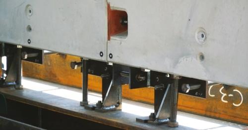 写真2■ PCa部材のトンネル縦断方向の連結部と下端の調整部。PCa部材は、側壁コンクリートを模したH形鋼の上に設置してある。専用治具やボルトを介して位置を調整し、PCa部材の設置後は治具をモルタルなどで埋める(写真:日経コンストラクション)