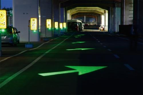 写真1■ 路面に矢印形の光を照射して試験している様子。工事の予告看板1枚につき1個の小型照明装置を取り付ける。通常、高速道路上で交通規制を伴う工事を実施する際は、規制箇所の手前に予告看板を設けてドライバーに告知していた(写真:阪神高速技術)