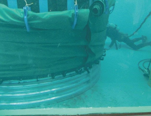 写真1■ ファスナー付きの防水シートをライナープレートに被覆している様子。仮留めを外して、シートを1枚ずつ引き上げ、ファスナーで連結しながら全体を覆っていく(写真:YKK)