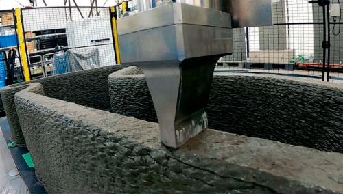 写真1■ 清水建設が開発したラクツムをコンクリート用3Dプリンターで積み上げている様子。厚さ0.7cm、秒速10cmのペースで押し出している。ノズルを変えることで、幅は2~8cmまで対応できる(写真:清水建設)