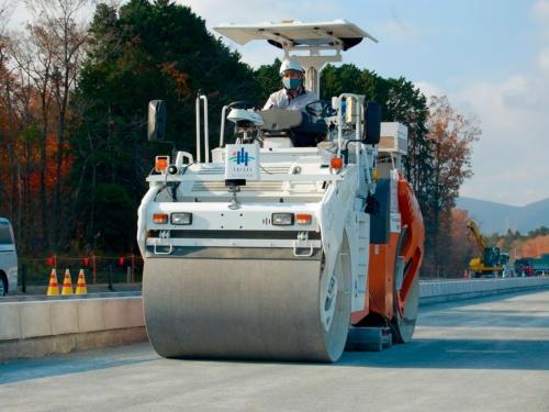 写真1■ 密度計と水分計を収納した車輪状の計測機器を、振動ローラーの前輪と後輪の間に設置した。静岡県御殿場市内で大成ロテックが施工中の138号BP水土野北地区舗装工事で、開発した技術を適用する様子を公開した。2020年11月18日撮影(写真:日経クロステック)