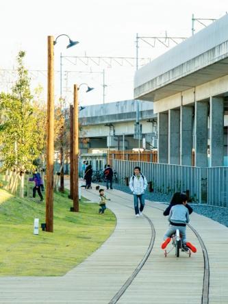 写真5■ 西側エリアの線路デッキ。木の照明柱が連なる。足元にある距離を示すサインは、九州大学の学生の手づくり。高架側の砂利舗装の下は70cm掘り下げて、雨水の一時貯留施設を設置している(写真:イクマ サトシ)