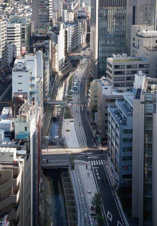 写真2■ 線路跡地を活用した渋谷リバーストリートの遊歩道の幅員は、約3~13.5m。舗装デザインは川の流れをイメージしている。渋谷ストリームエクセルホテル東急の13階から南東側を向いて撮影(写真:吉田 誠)