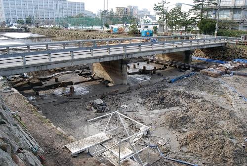 写真4■ 発掘調査ではコンクリート橋(1963年建造)の下の地盤から、69本の木製の橋脚遺構が出土した(写真:鳥取市)