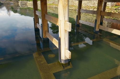 写真6■ 明治元年の橋脚遺構は、張り出した水中梁の下(復元橋の橋脚の真下)に位置する。水中梁の横に見える円形状の物体は、別時代の遺構(写真:生田 将人)