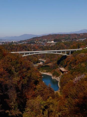 写真2■ 天龍峡大橋は、天竜川の浸食によって生まれた南北2kmにわたる渓谷の南端に架かる。川沿いをJR飯田線が走る。橋面上に線路への落下物防止柵を設ける代わりに、線路を覆う防護工を設置。橋をスレンダーに見せ、渓谷の景観を阻害しないようにした(写真:安川 千秋)