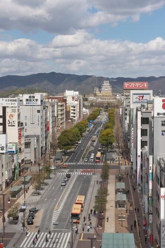 JR姫路駅側から見た大手前通り。写真中心部の交差点から奥側の約400m区間が南工区。交差点より駅側の約160m区間は、2015年にトランジットモール化し、バスやタクシー以外の一般車両の通行を禁止した。沿道の建物側に設けた歩行者の通行帯は、駅前から南工区へとアースカラーのレンガ舗装が連続する(写真:生田 将人)