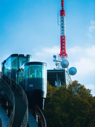 写真2■ スロープカーは1編成2両で、2編成が運行。最大で約20度の勾配をゆっくりと行き来する。写真奥は山頂駅。駅から200mほど離れた場所に展望台がある(写真:長崎市)