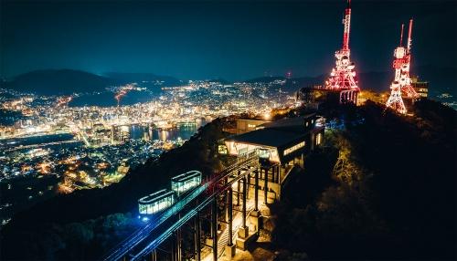 写真1■ 長崎市が整備した斜面走行モノレール「長崎稲佐山スロープカー」。夜景の名所である稲佐山山頂展望台(写真右奥)と山の中腹とを結ぶ輸送施設として2020年1月に開業した。レールの下には遊歩道が通る(写真:長崎市)