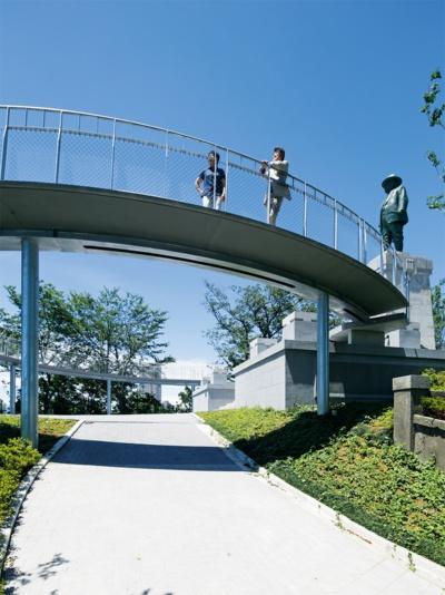 写真2■ 広場に続くアプローチから見る。写真右奥は学園創立者、浅野総一郎の銅像。空中回廊は銅像の台座につながり、銅像の表情が見てとれる高さに計画した。床版上面の最高高さは地面から3.4m。人が下を通るため、床版下面のデザインにも気を配った。7本ある鉄骨柱のうち、西側斜面寄りの5本は基礎同士を地中梁でつなぎ、安全性を高めた(写真:安川 千秋)