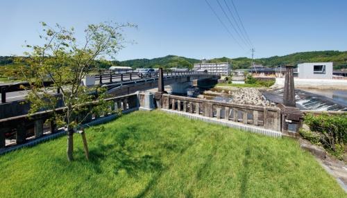 写真1■ 鹿児島県姶良市にある新山田橋の橋詰め付近に、県が芝生広場を整備。2019年3月に完成した。旧橋の面影を伝える親柱は、そのままの位置で保存した。左が2017年に供用を開始した新橋(写真:イクマ サトシ)