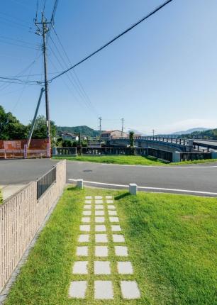 写真3■ 右岸側の道路を挟んで飛び地にあるテラス。旧山田橋が架かっていた軸線を強調するように白いタイルを並べた。新橋の奥に見えるのは桜島(写真:イクマ サトシ)
