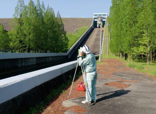 洪水吐きの表面に生じたひび割れを計測している様子。デジタルカメラに加えて、遠方からひび割れ幅を正確に計測できる専用の測定器も使用した(写真:クモノスコーポレーション)