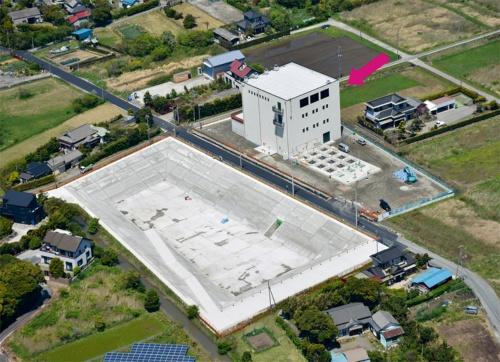 写真1■完成した木更津市金田西雨水ポンプ場。沈砂池ポンプ棟(矢印で示した建物)や、その左に見える雨水調整池など複数の施設で構成される(写真:前田建設工業)