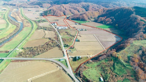 写真2■ 赤線で囲んだ範囲を整地するとともに、農道や用水路、排水路、農道などを整備し、既存の農地を拡張した(写真:斉藤建設)
