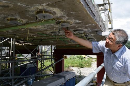 写真1■ 金沢大学の鳥居和之特任教授が指差すのは、表面設置型の陽極材。高速道路から切り出した劣化床版に取り付け、塩害環境下で効果を検証している(写真:日経コンストラクション)