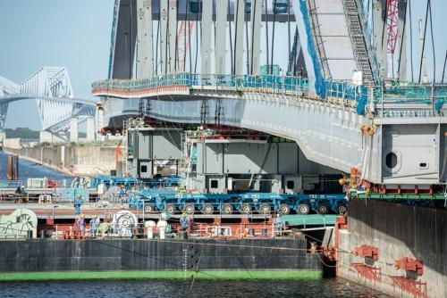 写真1■ 巨大なアーチを載せた多軸台車が、写真右手の地組みヤードから台船の上に移動する。2018年8月15日撮影(写真:大村 拓也)
