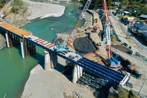 写真1■ 鎌瀬橋の仮橋の架設現場。仮橋の上部工は最大スパン24mに対応している。200tのクローラークレーンの積載荷重に耐えられる。2021年3月23日に撮影(写真:イクマ サトシ)