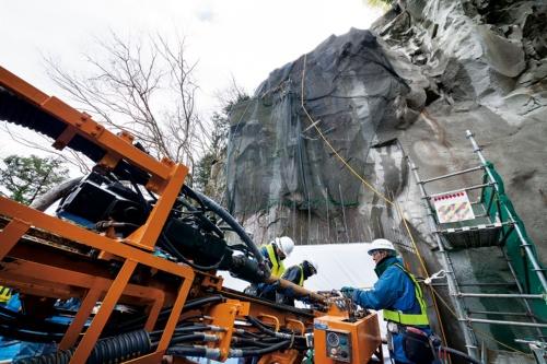 写真2 ■ 岩塊の表面を厚さ0.5~6m程度の直壁コンクリートで平らに覆った後、RPDで地山を削孔する。18年3月に撮影した時点で、下から2段目のアンカーを施工していた(写真:吉田 誠)