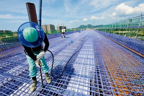 写真1■ コンクリートの打設を目前に控えた中空床版橋。エポキシ樹脂塗装鉄筋の下に、埋設型枠の発泡スチロールが見える。放水ノズルを差し込み、底面の型枠上のごみなどを取り除く(写真:日経コンストラクション)