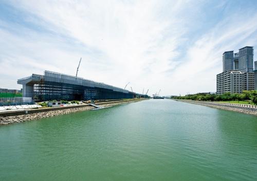 写真2■ 写真の左手前に長さ280mのPC7径間連続中空床版橋、その奥に同244.5mのPC6径間連続中空床版橋を架設する。前者は三井住友建設・みらい建設工業JVが、後者は五洋建設・ドーピー建設工業JVがそれぞれ施工している。写真右がアイランドシティで、海沿いに遊歩道や公園が整備されている(写真:日経コンストラクション)