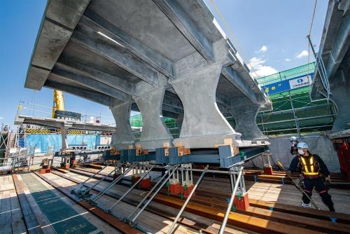 写真1■ 台車に載せたDura-Bridgeのフルプレキャストセグメントを支保工上でスライドさせて並べる。標準セグメントの重量は20t。左奥のセグメントは偏向部(写真:大村 拓也)