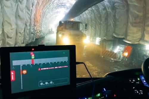 写真1■ 運転席から見た坑内の様子。タブレット端末に表示される自車と他車の位置を基に、離合場所で効率的にすれ違えるようになる(写真:鹿島)