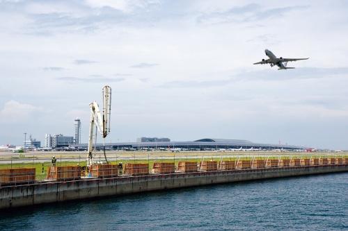 写真1■ かさ上げ工事が始まった関空1期島の東側護岸をオイルタンカーバースから見る。1日当たりのコンクリート打設量は100m3ほど。2020年度から護岸前面に消波ブロックを設置する工事も始まる(写真:日経コンストラクション)