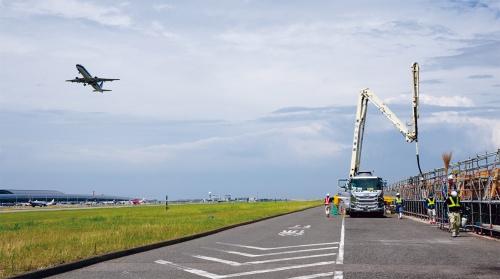 写真2■ 航空機が離発着する滑走路のそばで施工する。1期島は現在も洪積層の圧密が続き、年間6cmほどのペースで沈下している(写真:日経コンストラクション)