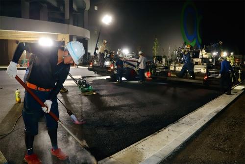 写真1■ 日本最大級となるGLPの物流拠点の外構部で、廃ペットボトル入りのアスファルト混合物「スーパーPETアスコン」を舗設している。2021年8月19日深夜に撮影(写真:安川 千秋)