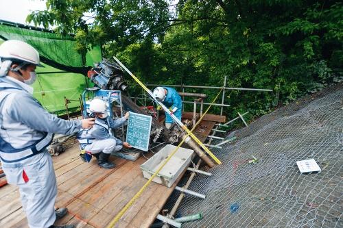 写真1■ 松山自動車道の河之内地区の法面工事の現場。グラウンドアンカーの削孔完了後、施工者がカメラを持って、ケーシングに入れた検尺棒の残尺を撮影している(写真:日経コンストラクション)