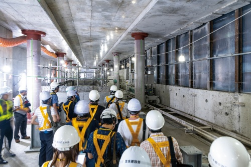 写真1■ 地下1階レベルを走る日比谷線の既設トンネルの左右に、新駅のプラットホームが収まる躯体を構築した。写真右が既設トンネルで、ワイヤソーなどでブロック状に切断した側壁をリフト付き台車に載せ替え、レール上を運搬して撤去する。側壁を撤去した部分は、日比谷線の軌道と工事エリアを隔てる防護用の鉄板が露出している。左奥の開口は地下2階へ通じる階段。都市再生機構と東京メトロが2019年8月下旬、報道陣に現場を公開した