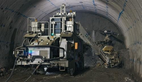 写真2■ トンネル坑内に設けた制御室から、マシンガイダンス機能付きのドリルジャンボを遠隔操作している。せん孔作業中は切り羽周辺に人は立ち入らない(写真:生田 将人)