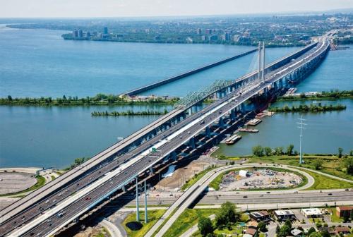 写真1■ セントローレンス川に架かる全長3.4kmのサミュエル・ド・シャンプラン橋を右岸側から見る。上り線と下り線の間には将来、次世代型路面電車(LRT)が走る計画がある。隣に架かる旧橋は今後、解体する。2019年7月撮影(写真:Signature on the Saint Lawrence)
