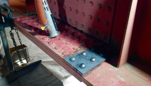 写真2■ 添接板の手前側がクーレーザーで施工を終えた範囲。作業時間は3分ほど。塗装の塗り替え工事で最初に必要な下地処理のうち、古い塗膜などを全て除去して鋼材の下地を露出させる「1種ケレン」の素地調整ができる。筒先のオレンジ色のホースは集じん機につながる(写真:日経コンストラクション)