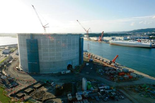 写真1■ 東京ガス日立LNG基地に立ち上がったプレストレスト・コンクリートの防液堤を海側から望む。プレキャスト部材間を現場打ちしたため、表面に格子状の模様がうっすらと浮かぶ。撮影した2019年9月時点で防液堤はほぼ完成し、内部で鋼製タンクの工事が進む。写真左奥は久慈川(写真:日経コンストラクション)