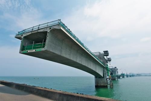 写真1■ 手前に見えるのは左岸側のP1橋脚。台船でセグメント桁を運んで、吊り上げて架設する。2020年7月20日撮影(写真:生田 将人)