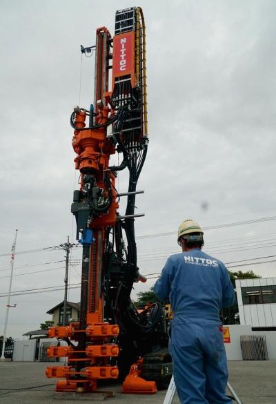 写真1■ 日特建設などが開発したハイグランツドリル。2020年11月に埼玉県久喜市の中央機材センターで公開した。高さは8mで、輸送時は折りたたむ。手前は操縦者(写真:日経クロステック)
