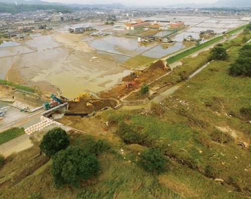 写真1■ 決壊した小田川の堤防。荒締め切りの後、市街地側に鋼矢板を打設した。2018年7月11日撮影(写真:国土交通省)