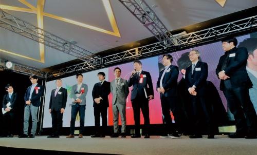 写真1■ 「ICIイノベーションアワード」の授賞式。受賞者に囲まれ、中央でマイクを握るのが、審査委員長を務めた前田建設工業の前田操治社長(写真:日経コンストラクション)