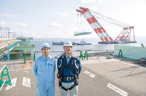 写真2■ 再架設当日、復旧現場に立つ西日本高速道路会社の佐溝純一橋梁担当部長(左)とIHIインフラシステムの内田裕也課長。海上には台船から鋼箱桁を吊り上げた起重機船「武蔵」が待機する。関空にとって連絡橋は唯一の陸上アクセスルートだ(写真:大村 拓也)