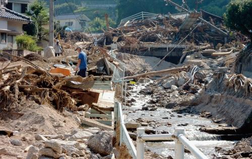 写真1■ 上流から流れてきた巨石や流木が橋に引っ掛かり、河道を閉塞した広島県坂町の様子。土砂が住宅地にあふれた(写真:日経コンストラクション)