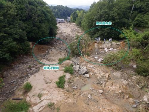写真1■ 西日本豪雨で決壊した、広島県の勝負迫下池。上流のグラウンドが崩壊して土砂が流入したことで、越流が生じた。ため池下流で1人が死亡し、4人が負傷した(写真:農林水産省中国四国農政局)
