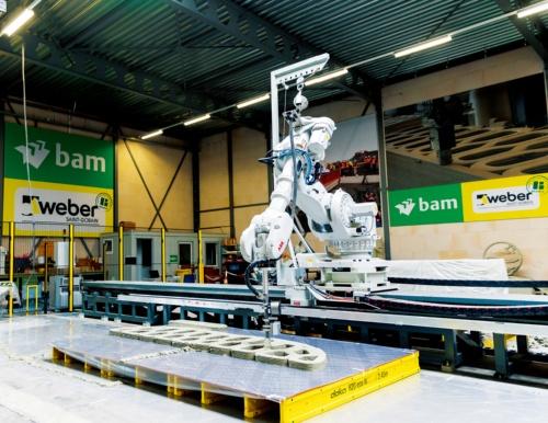 写真1■ セメント系材料用の3Dプリンター工場で新しい橋のパーツを製造するデモンストレーションの様子。ロボットアーム型の3Dプリンターで、モルタルを層状に重ねていく(写真:BAM Infra)