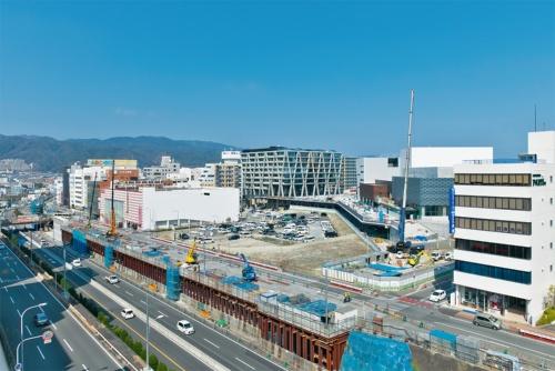 千里中央駅(大阪府豊中市)から箕面萱場駅(同箕面市)に向けて延伸工事が進む北大阪急行線(以下、北急)。その中間に設けられる新駅・箕面船場阪大前駅の周辺では箕面市の複合施設(2021年5月オープン)や大阪大学の箕面キャンパス(21年4月開校)など、開発が進行中だ。写真は、建設中の新駅・箕面船場阪大前駅とその周辺を南西から見たところ。延伸事業は当初、2020年度の開業予定だったが、用地買収の遅れや計画地の地中に残置された構造物が見つかったことから3年延びて23年度となった(写真:生田 将人)