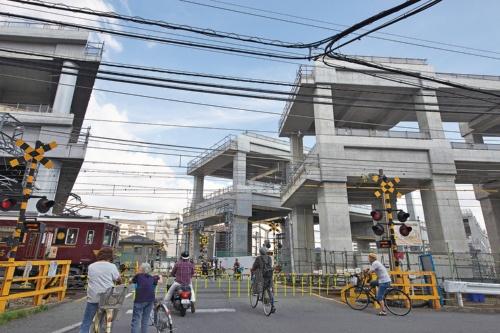 1⃣ 高架橋の建設が進む中、淡路駅南側の踏切で通過列車を待つ人々。京都線の踏切(手前)の向こうに千里線の踏切が続く。一度に渡りきれず、間で取り残される人も多い(写真:生田 将人)