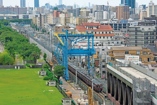 2⃣ 淡路駅から南に延びる京都線。高さ約26mの青い直上施工機を使って、地上を走る線路の真上に高架橋を築く。線路の両側に橋脚が立ち並ぶ(写真:生田 将人)